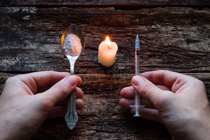 Intoxiqué masculin tenant la seringue et la cuillère à côté d'une bougie photos stock