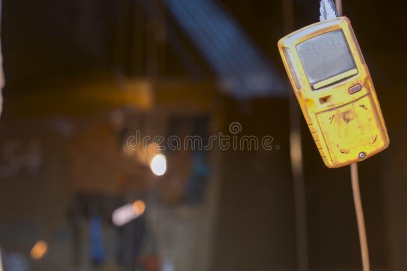 Intoxique o detector do teste que pendura no quadro de janela quando equipamento de segurança vestindo do soldador obscuro do ace imagem de stock