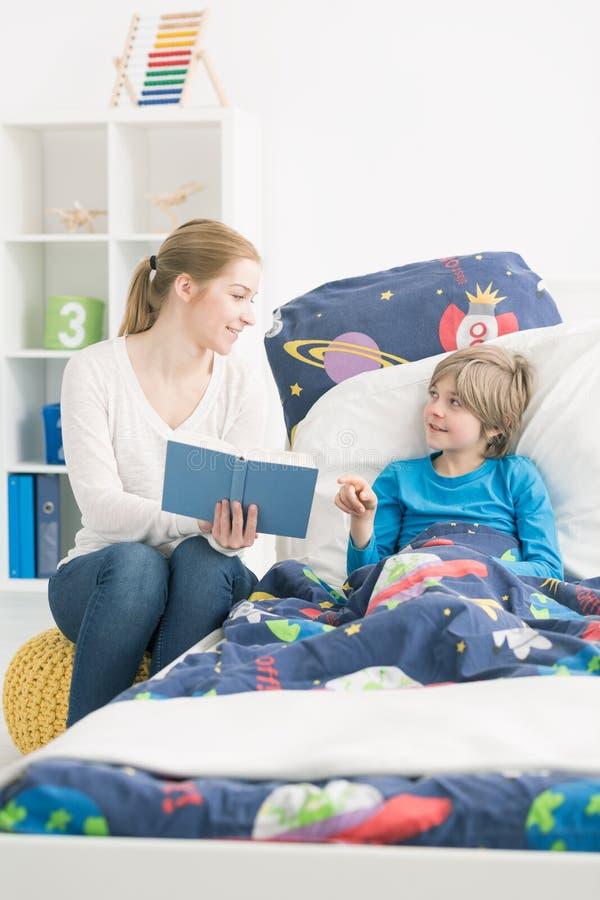 Intrattenere il suo piccolo figlio durante la sua malattia immagini stock libere da diritti