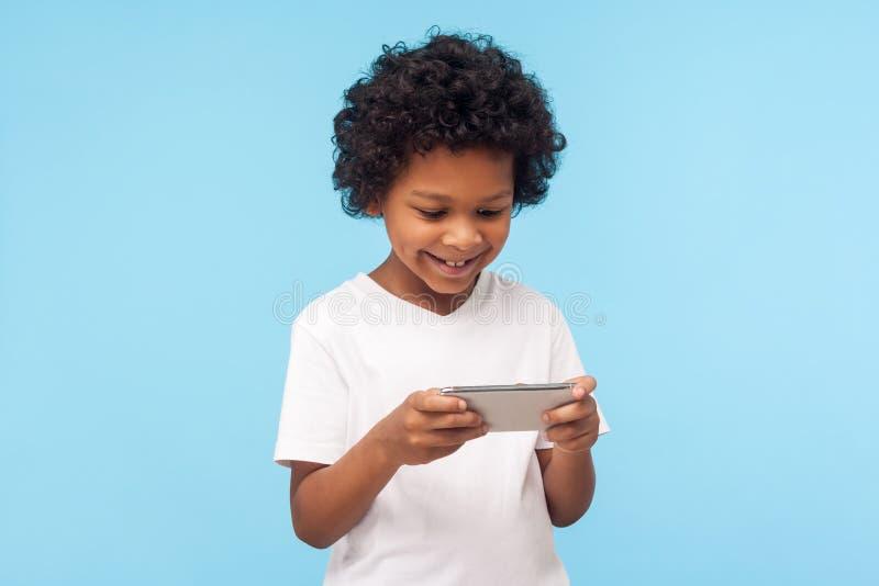 Intrattenimento e tecnologia per bambini Felice ragazzo carino con i capelli ricci con il cellulare immagine stock