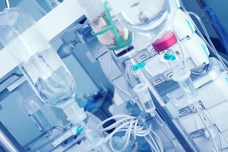 Intravenous drip with saline bottles on the background of digital equipment stock image