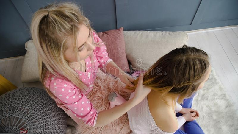 Intrecciatura dei capelli delle ragazze del bff di svago di amicizia fotografia stock libera da diritti