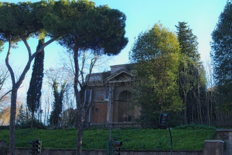 Intressera och ett mycket gammalt hus döljer bak träden roma italy royaltyfri foto