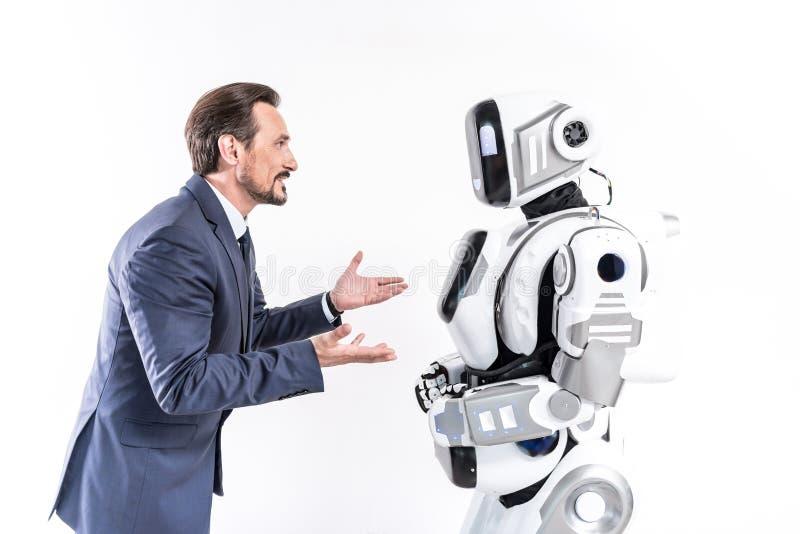 Intresserad chef som talar med cyborganställd royaltyfri fotografi