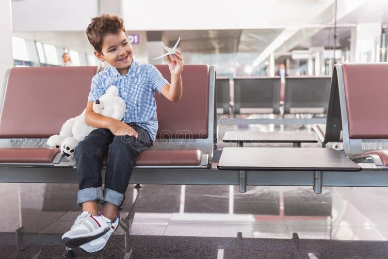 Intresserad le gossebarn som lokaliserar på terminalen fotografering för bildbyråer