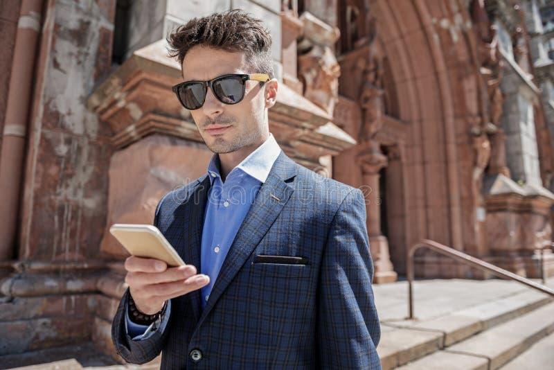 Intresserad manlig person som använder smartphonen royaltyfri bild