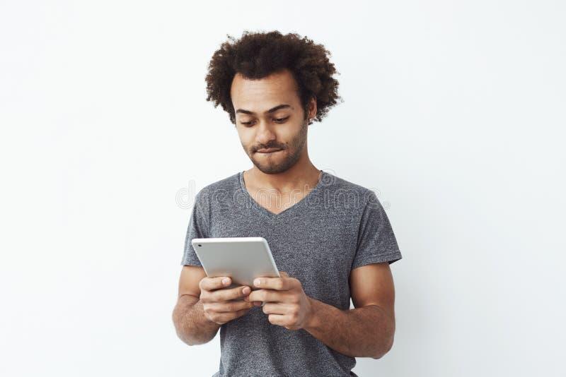 Intresserad och koncentrerad ung afrikansk man som ser minnestavlan som spelar en platformerlek och över tycker om nya nivåer royaltyfria bilder