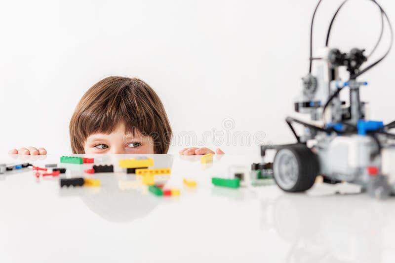 Intresserad slug gossebarn som kastar en blick på leksaken royaltyfria foton