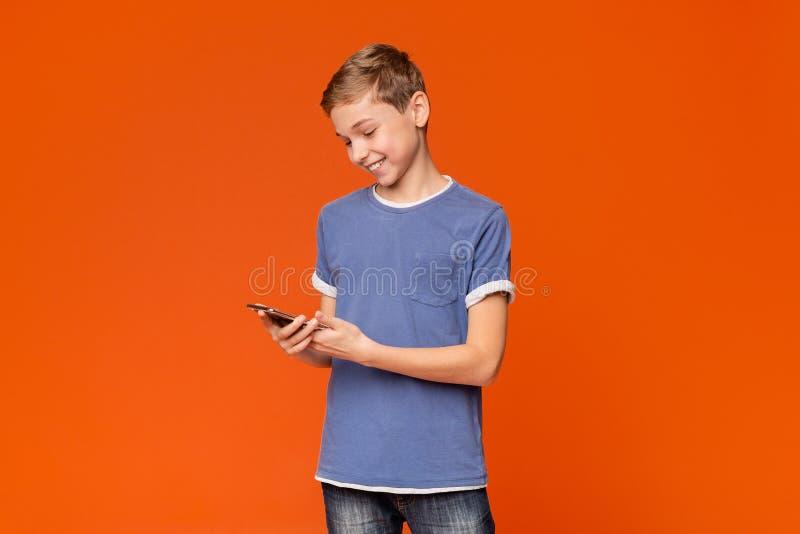 Intresserad tonårig pojke som använder smartphonen på orange bakgrund royaltyfri bild