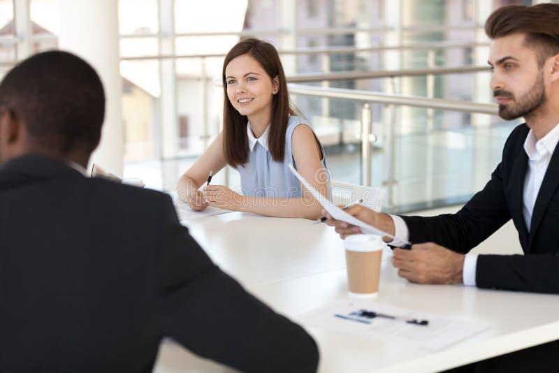 Intresserade anställda som sitter på förhandsmöte, lyssnar till kollegan royaltyfria bilder