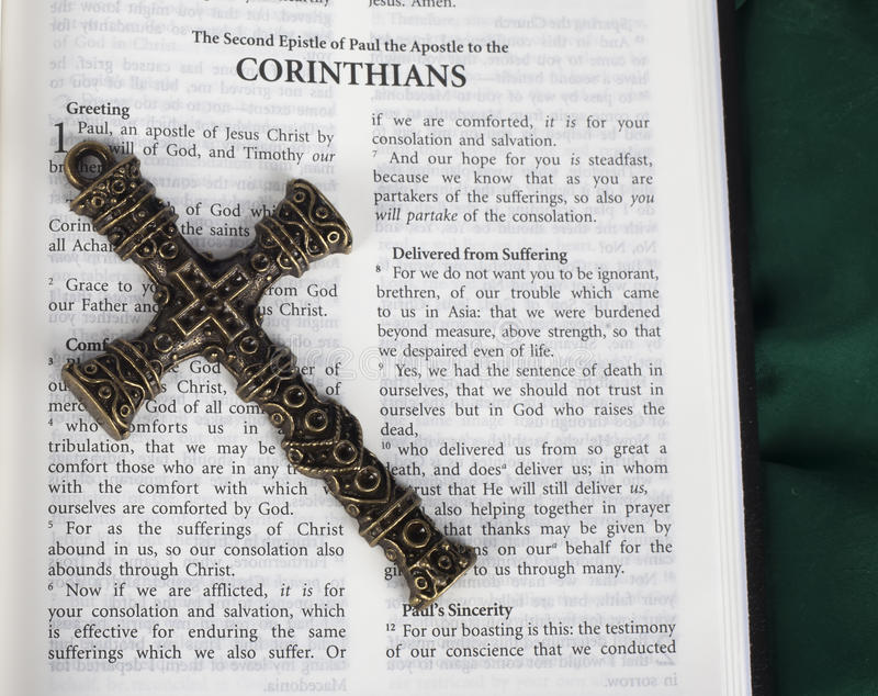 Intricate antique cross with Corinthians verse in Holy Bible royalty free stock images