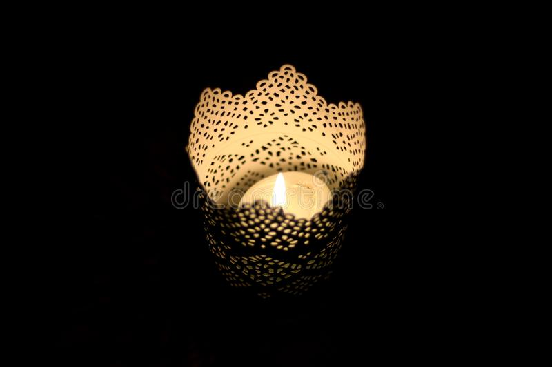 Candle Holder. Intricate candle holder with lit candle in the dark. Black background, selective focus, copy space royalty free stock photo
