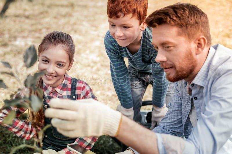 Intrigieren Sie die lächelnden wartenden Kinder wenn Baumwachsen lizenzfreies stockbild