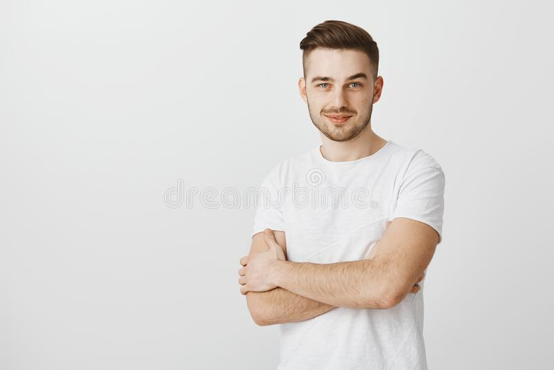 Intrigierter intelligenter junger männlicher Unternehmer im weißen T-Shirt mit dem smirking Händchenhalten des Schnurrbartes kreu lizenzfreie stockbilder