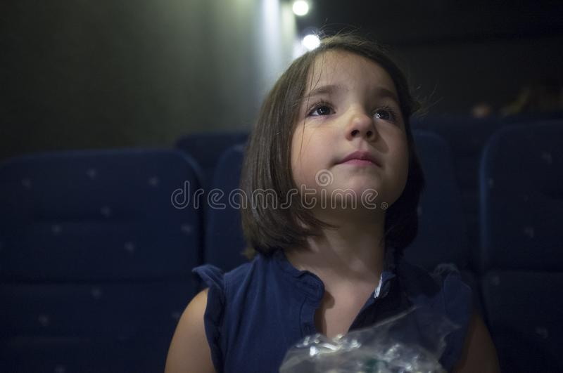 Intrigued child girl at cinema. Real scene. Child girl watching film at real cinema. She is got a intrigued expression royalty free stock photography