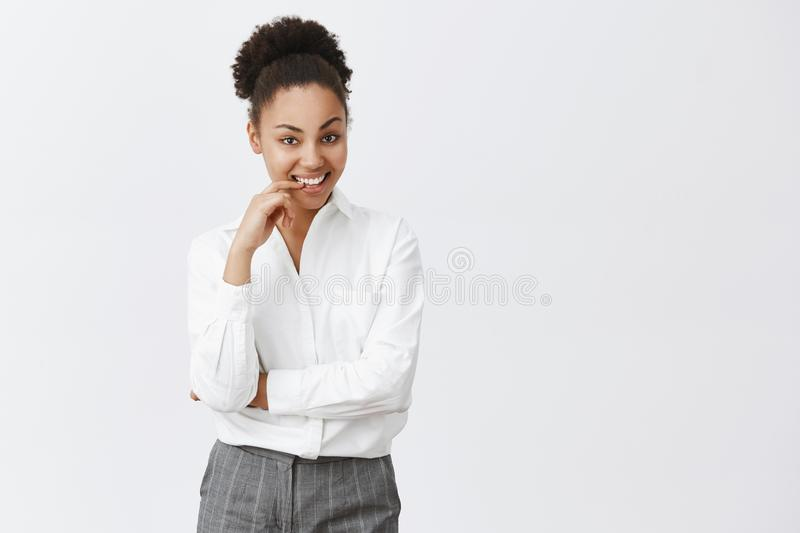 Intrigued coworker listenng dirty stories with smirk. Curious charming and playful african female in white shirt and. Pants, biting finger flirty and smiling stock photos