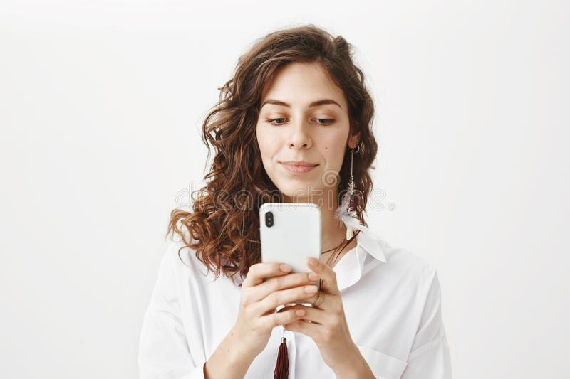 Intrigued and positive sensual caucasian woman with curly hair holding smartphone while messaging or playing games. Standing over gray background in good mood royalty free stock photos