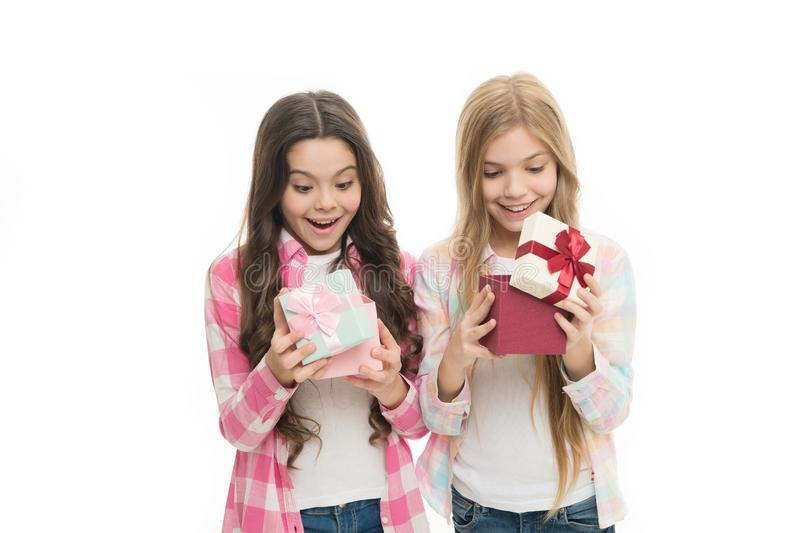 Intriguing moment. Birthday present. Girls sisters or friends hold gift boxes. Small girls open holiday present. Children excited cheerful faces hold presents stock photography