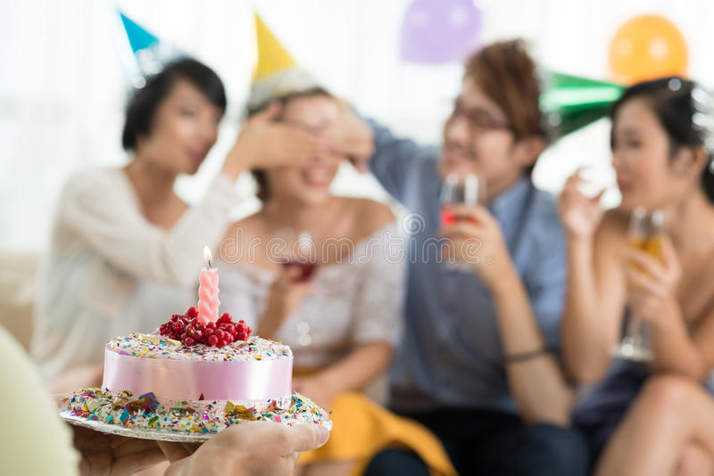 Introduction of a cake. Man bringing a cake to his friends at party royalty free stock photo