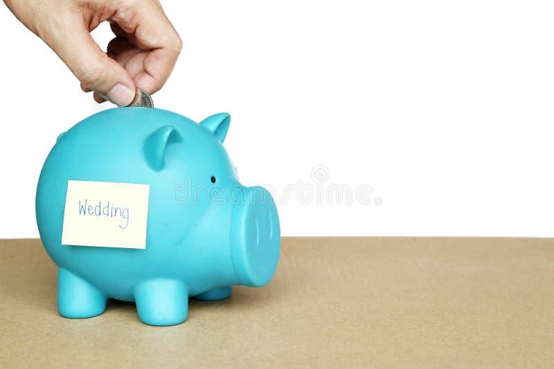 Introduza moedas no mealheiro azul com nota e palavra pegajosas do casamento no conceito do dinheiro da economia para o casamento fotografia de stock