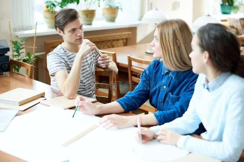 Introspectieve studenten die schets zich samentrekken stock afbeelding