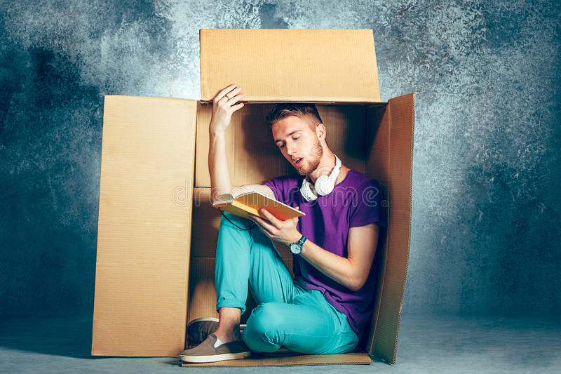 Introvert concept. Man sitting inside box and reading book. Introvert concept. Man sitting inside box and reading a book royalty free stock images