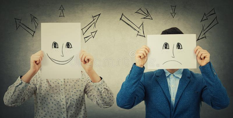 Introvert vs extrovert. Businessman and businesswoman covering their faces using sheets with drawn happy and sad emoticons, like a mask to hide her real emotion stock images