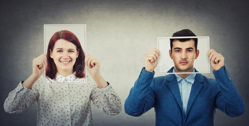 Introvert vs extrovert. Businessman and women covering their faces using photo sheets with happy and sad portrait emoticon, like a mask to hide the real emotion royalty free stock images