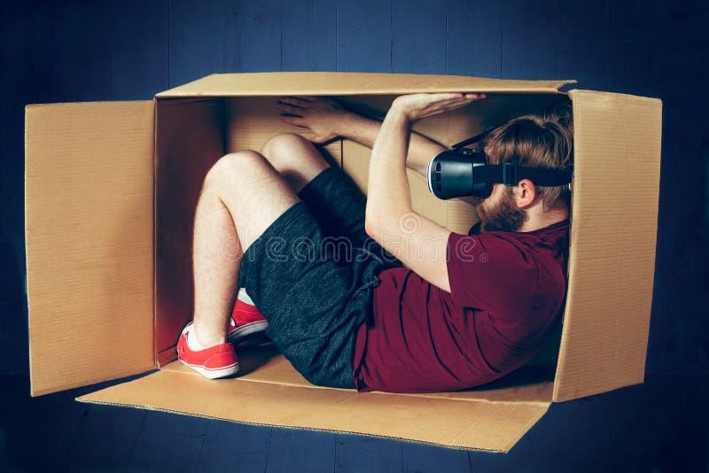 Introvertiertekonzept Der Mann, der innerhalb des Kastens mit Gläsern virtueller Realität sitzt Zukünftiges Technologiekonzept stockfotografie