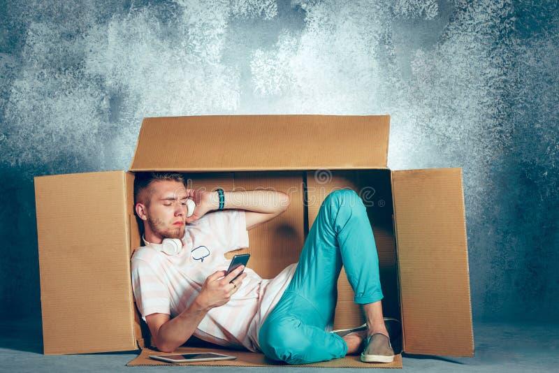 Introvertiertekonzept Mann, der innerhalb des Kastens sitzt lizenzfreies stockbild