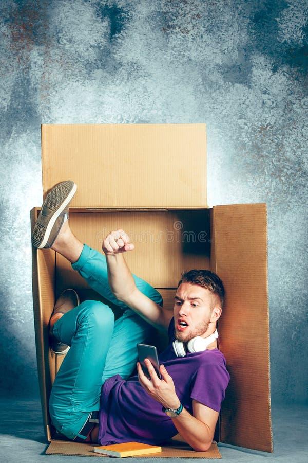 Introvertiertekonzept Mann, der innerhalb des Kastens sitzt lizenzfreie stockfotografie