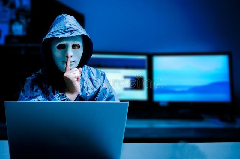 Intru anonyme dans le masque et le hoodie blancs Visage foncé obscurci faisant pour faire taire le geste sur le fond foncé, voleu photos stock