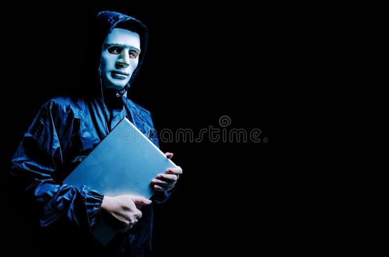 Intru anonyme dans le masque et le hoodie blancs Le visage foncé obscurci juge un ordinateur portable serré dans des ses mains, v image stock