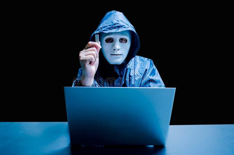Intru anonyme dans le masque et le hoodie blancs Le visage foncé obscurci tient une commande instantanée d'USB dans des ses mains images libres de droits