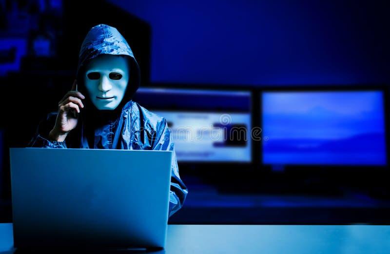 Intru anonyme dans le masque et le hoodie blancs Visage foncé obscurci utilisant l'ordinateur portable pour l'attaque et appeler  photographie stock libre de droits