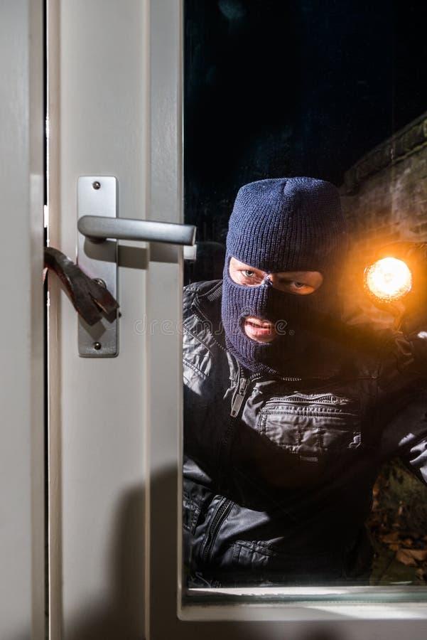 Intruso mascarado que guarda a tocha ao tentar à janela aberta com c imagem de stock