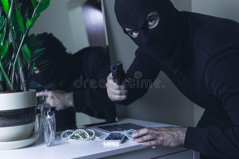 Intruso mascherato con la pistola fotografie stock