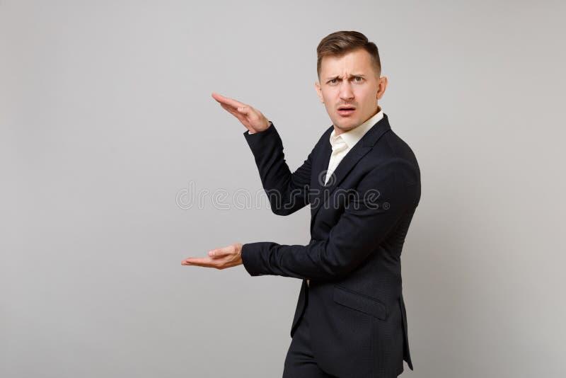 Intrygujący młody biznesowy mężczyzna gestykuluje w klasycznym czarnym kostiumu demonstrujący rozmiar z pionowo kopii przestrzeni fotografia royalty free