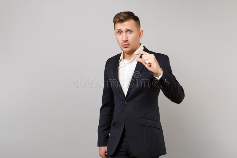 Intrygujący młody biznesowy mężczyzna w klasycznym czarnym kostiumu, koszula gestykuluje demonstrujący rozmiar z kopii przestrzen obrazy royalty free