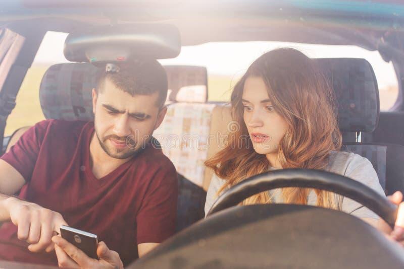 Intrygująca para siedzi w samochodzie, brodatych mężczyzn chwytów mądrze telefon, używa online mapy, próby znajdować sposób, gubj obraz royalty free