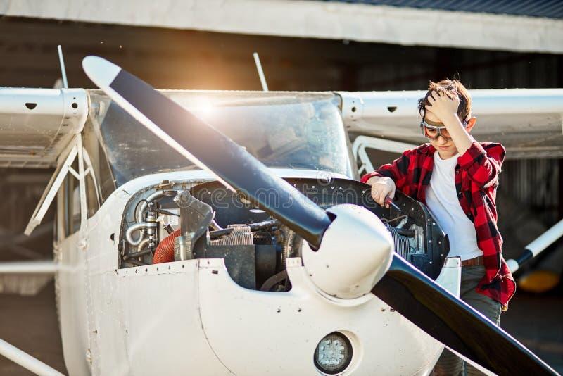 Intrygujący chłopiec stojaki blisko otwierali samolotu motorowego gabineta, próby załatwiać niepowodzenia fotografia royalty free