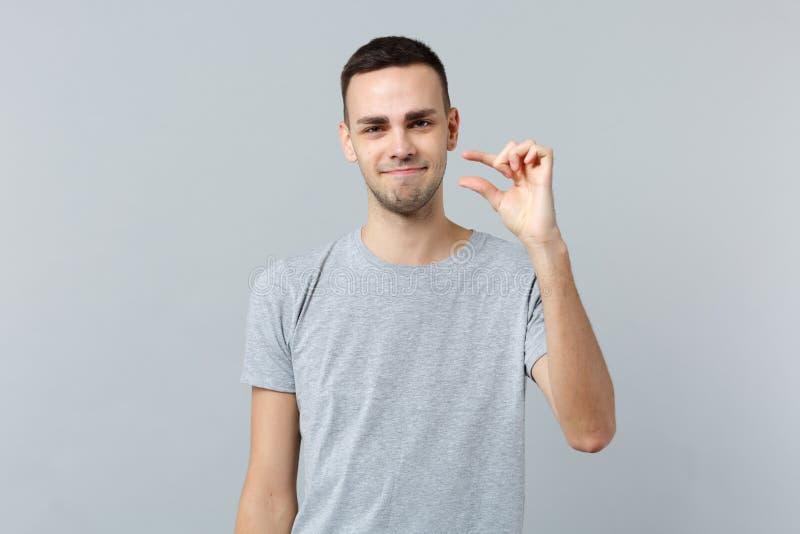 Intrygujący młody człowiek gestykuluje w przypadkowych ubraniach demonstrujący rozmiar z workspace odizolowywającym na popielatym fotografia stock