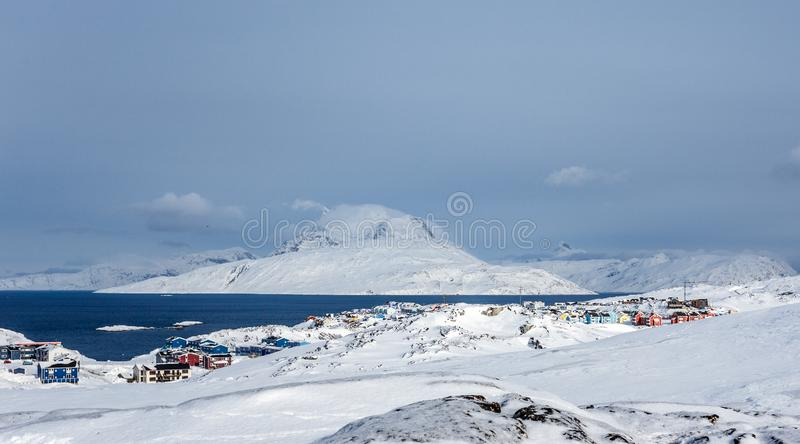 Inuit houses and cottages scattered across snow tundra landscape in residential suburb of Nuuk city with fjord and mountains in stock photos