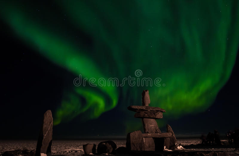 Inuit hudson bay northern lights. The aurora borealis, behind an inuit structure, with photographers enjoying the northern lights stock image