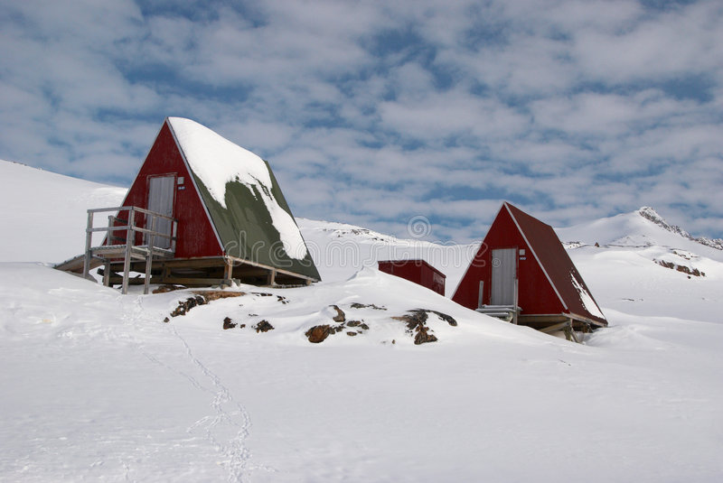 Inuit hut. Two coloured inuit huts in snow, Greenland stock images