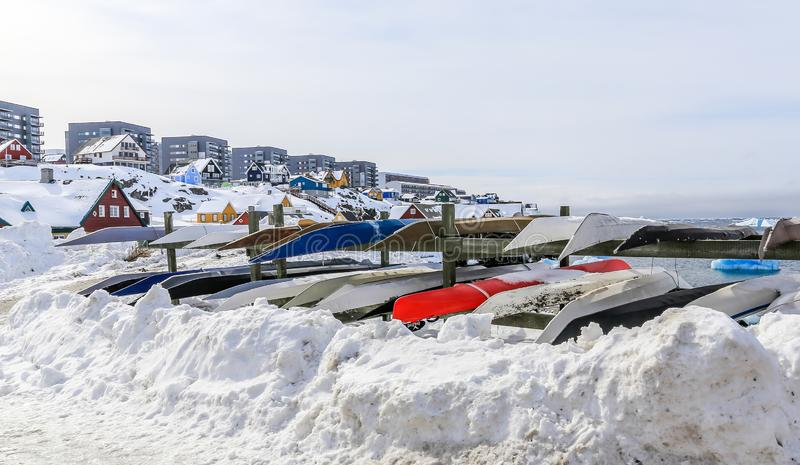 Inuit kayaks stored for a winter time in snow with Modern buildings and small cottages in the background, Nuuk old city harbor,. Greenland8 iceberg architecture stock images