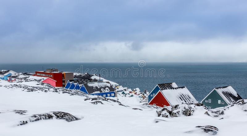 Inuit village houses covered in snow at the fjord of Nuuk city, Greenland. Architecture arctic bay beauty buildings capital cityscape climate cold colors royalty free stock image