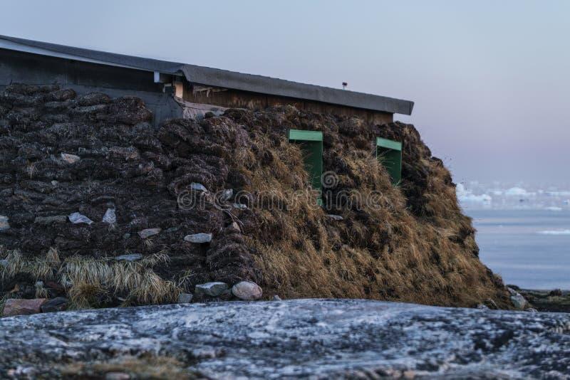 Inuithus och isberg på det arktiska havet i Grönland arkivbilder