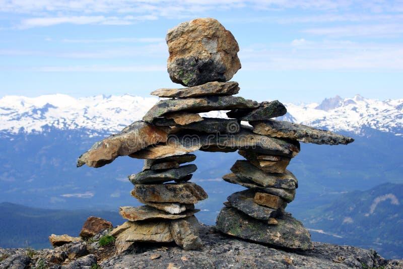 Inukshuk, Canada. Inukshuk and Canadian Rockies at Mt Whistler, Canada royalty free stock image
