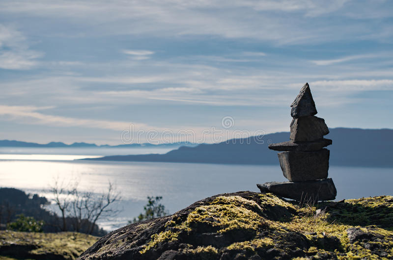 Inukshuk. An Inukshuk with an the ocean and mountains in the background royalty free stock image